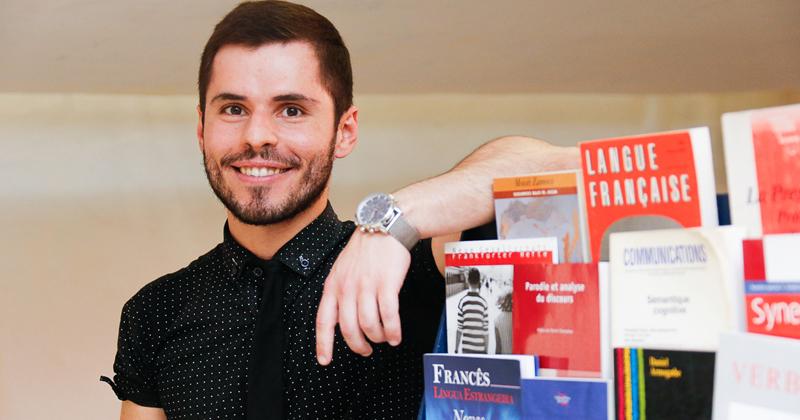 Pesquisador Artur Modolo apoiado em uma estante de livros