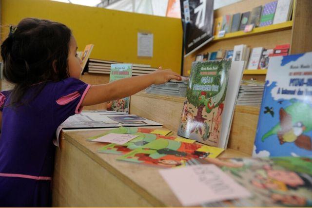 Criança pegando livros – Tânia Rego