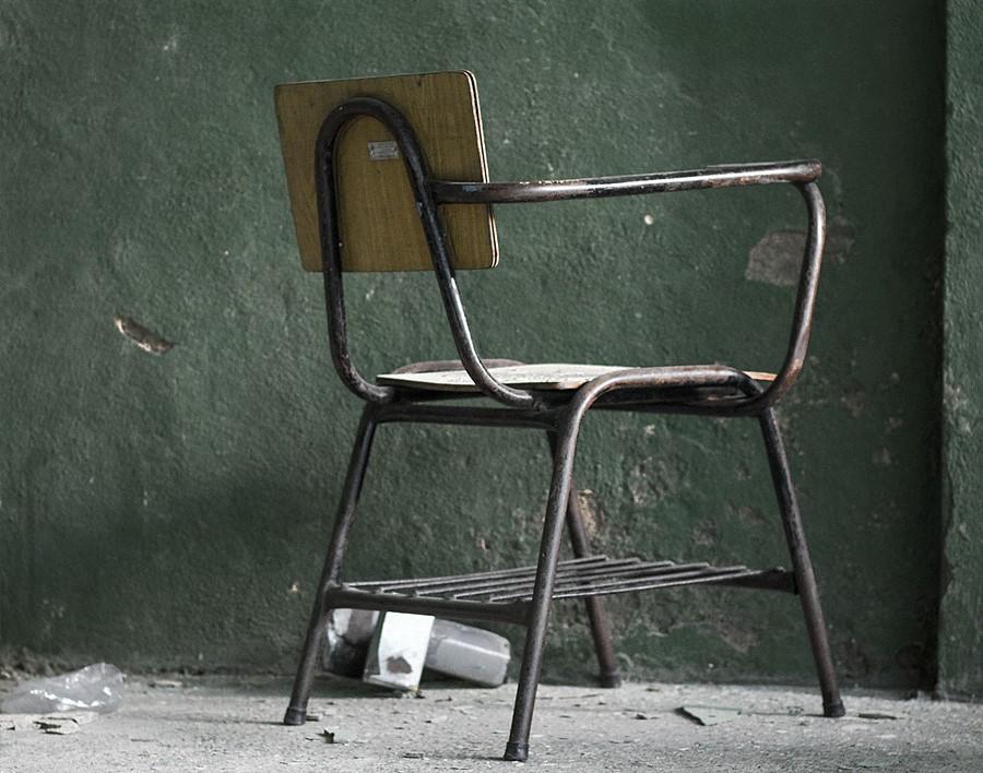 Uma Carteira Escolar Vazia Em Frente à Uma Parede Mau Cuidada